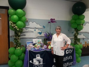 mrs alma oliva tai chi instructor infront of the display table