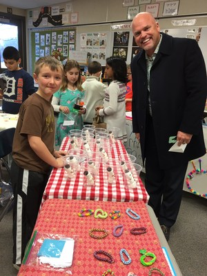 superintendent with student illustrating items for sale