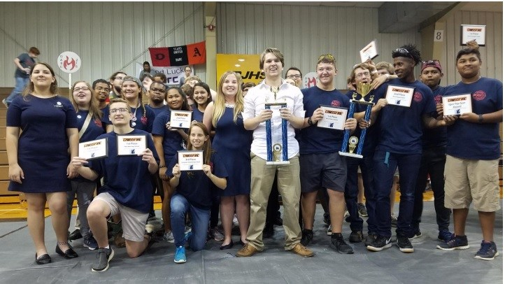 a photo of the students on the DARC robotics team with certificates and trophies