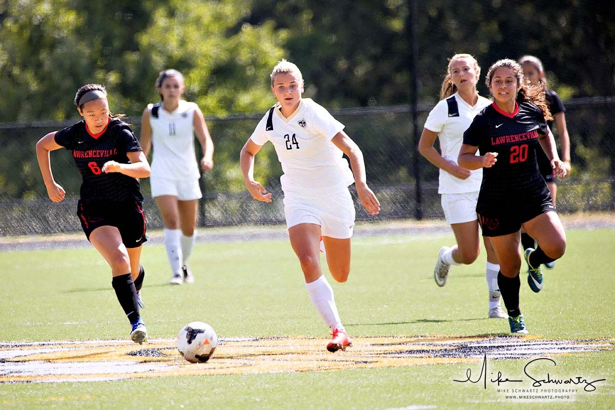 CHS girls soccer players pursue the ball down the field