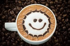 Picture of a cup of coffee with a foam smiley face.