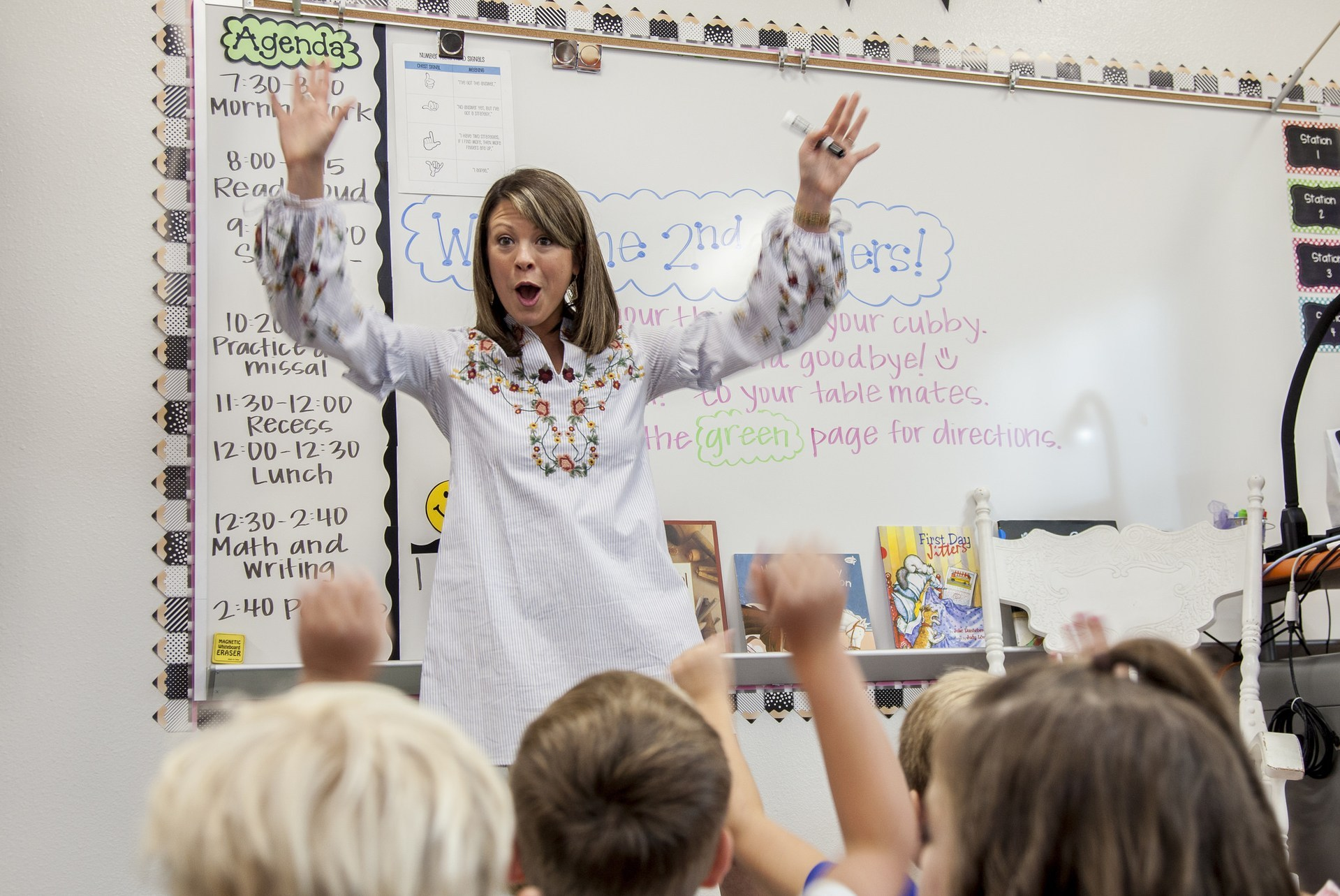 An elementary school teacher engages with her students on the first day of school