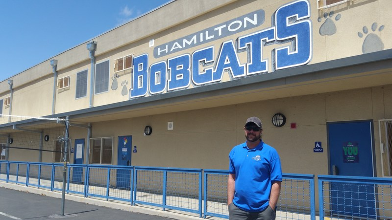 Lance Fogle in front of a Hamilton School sign.
