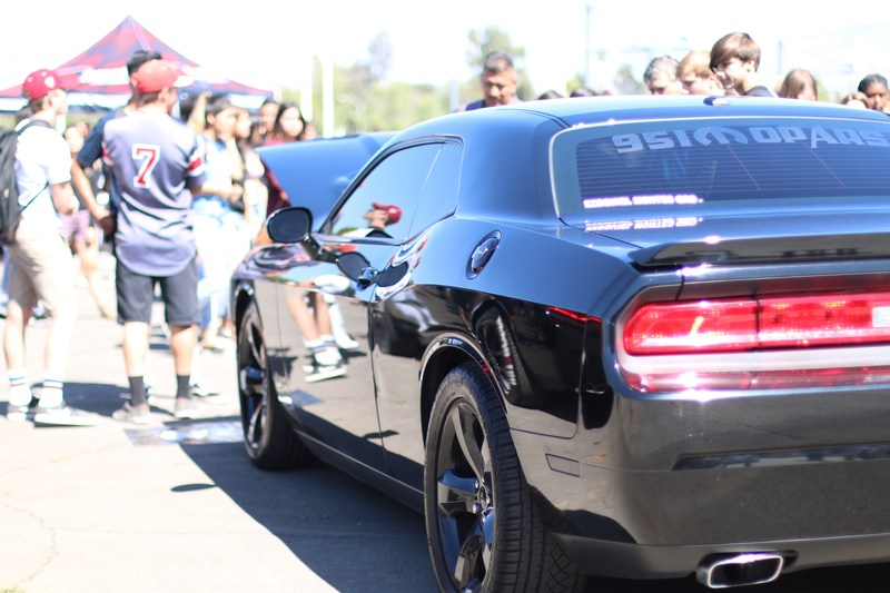 Students standing around a Dodge Challenger