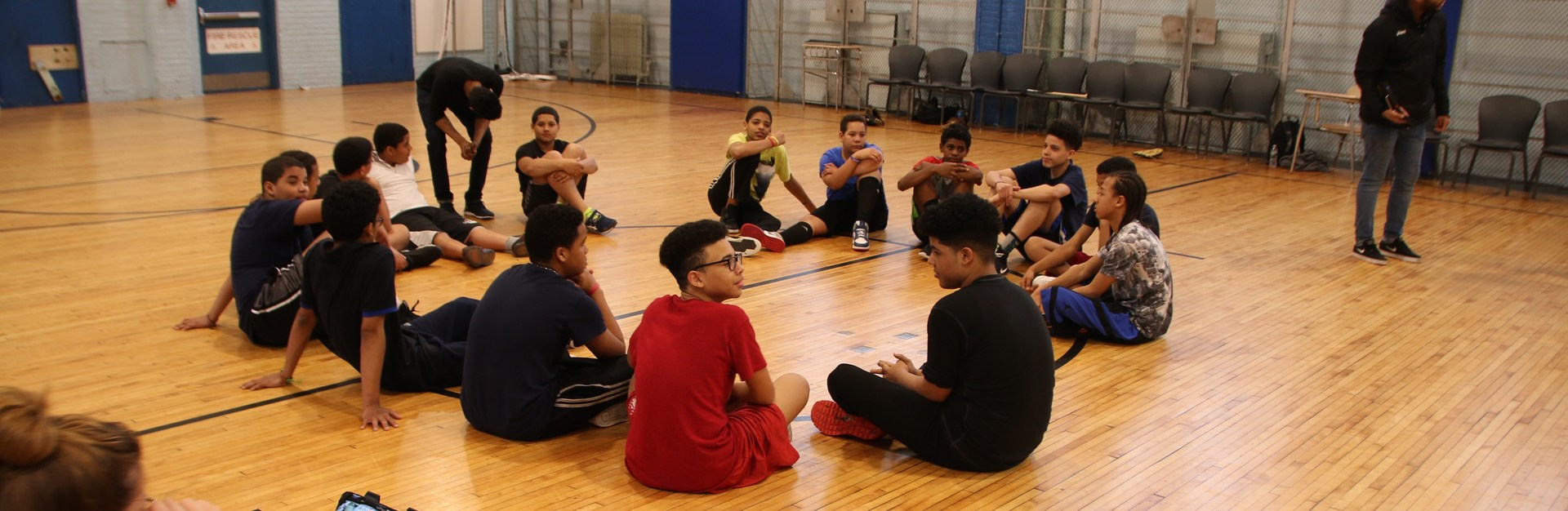 A group of boys sitting in a circle in the gym