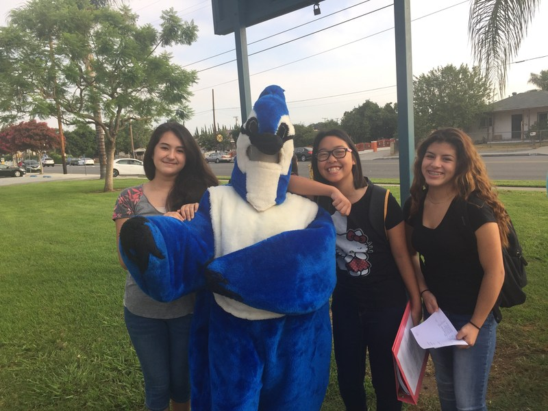 Returning eighth-graders cluster around their friend, Precious Lemus, dressed as Jones Junior High's Blue Jay mascot on Aug. 11, the first day of school for Baldwin Park Unified.