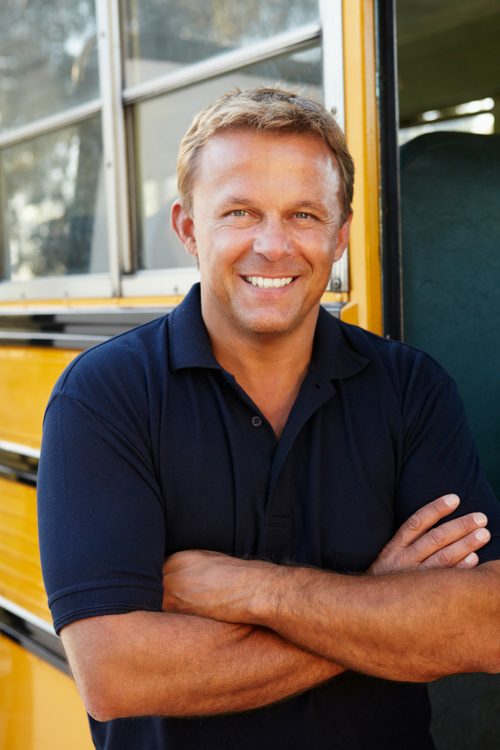 man in blue shirt smiling outside a school bus