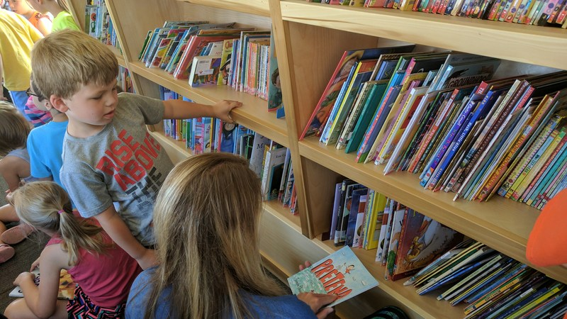 Students pick out books on board the mobile library.