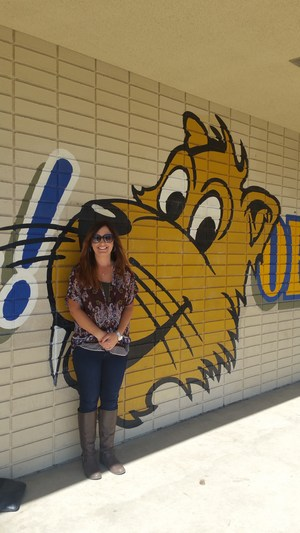 Angela Kramer in front of a Whittier sign.