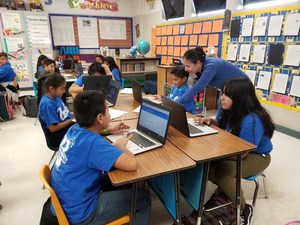 PUSD_KENMORE_1: Kenmore Elementary School teacher Raquel Gonzalez works with students to complete a response to literature. The students are clad in UCLA gear as part of the school's effort to foster a college-going culture.