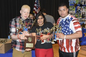 Students showing off their trophies and awards.