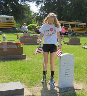 Eighth graders place American flags at grave sites of veterans.