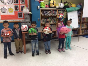 Students posing with their pumpkin in the library.