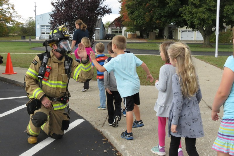 A firefighter in full gear high fives kids.