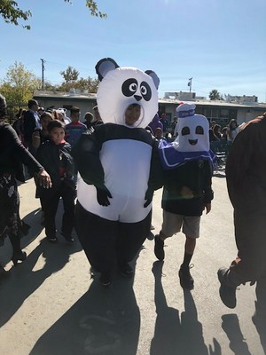 A student marching in a panda costume during the costume parade.