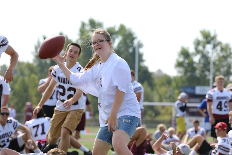 girl with glasses and white jersey prepares to throw football