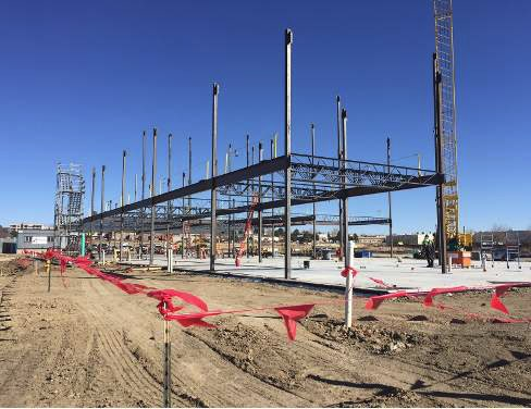Steel framework of building against a blue sky surrounded by a fence of red flags