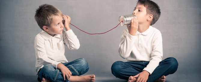 Two children talking over soup-cans tied together with a red string.