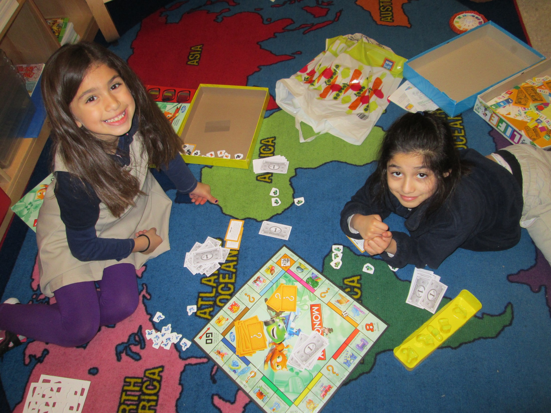 girls playing a board game on the floor