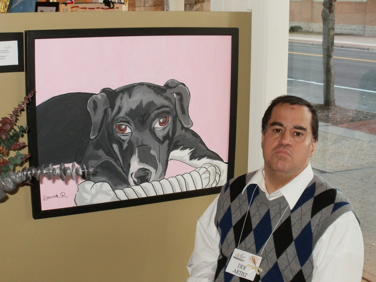 Man in art gallery with his painting of a dog