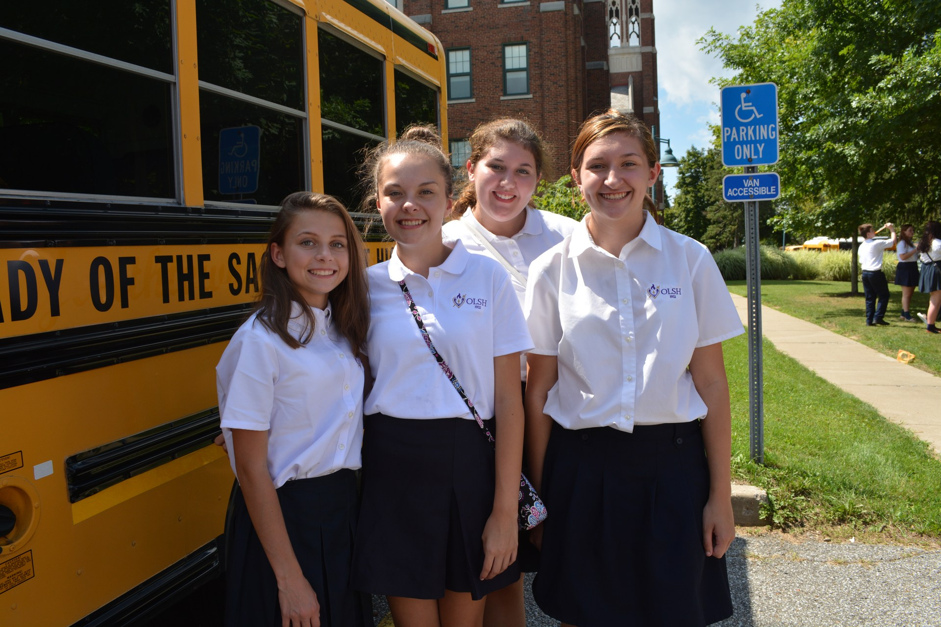 students at OLSH pose in front of the OLSH school bus