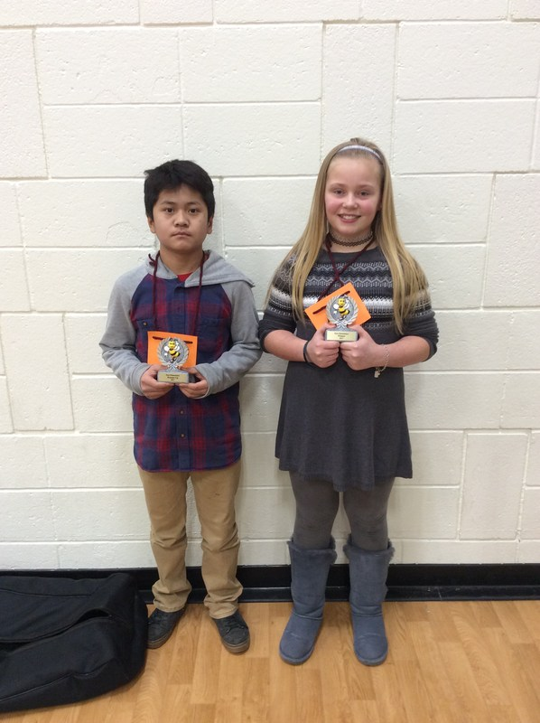 boy and girl stand with their awards against brick wall
