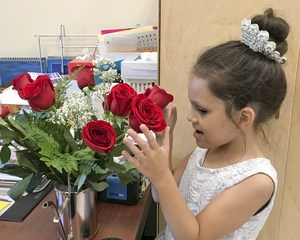 Young Schermerhorn girl smells the roses on the teacher's desk.