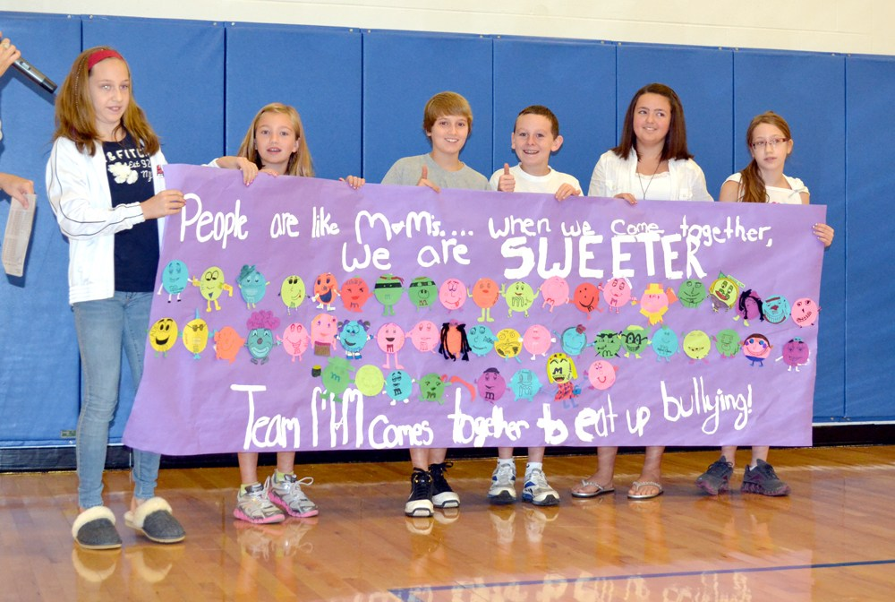 Students holding a banner listing positive messages.