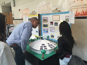 Superintendent listening a female student explain her project at the STEM Expo