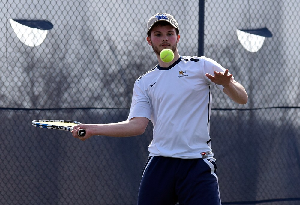 boy swinging tennis racquet