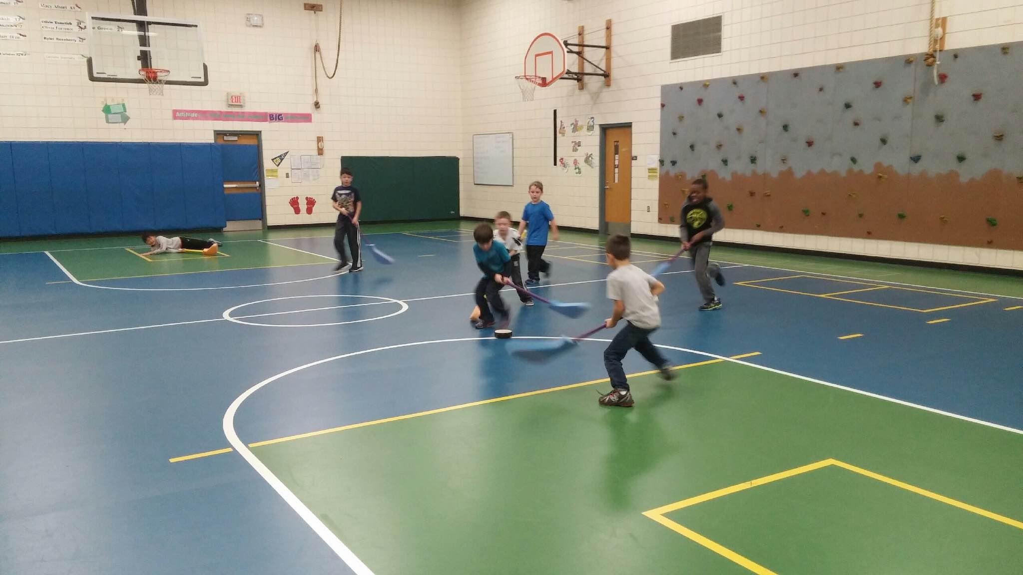 Boys playing floor hockey.