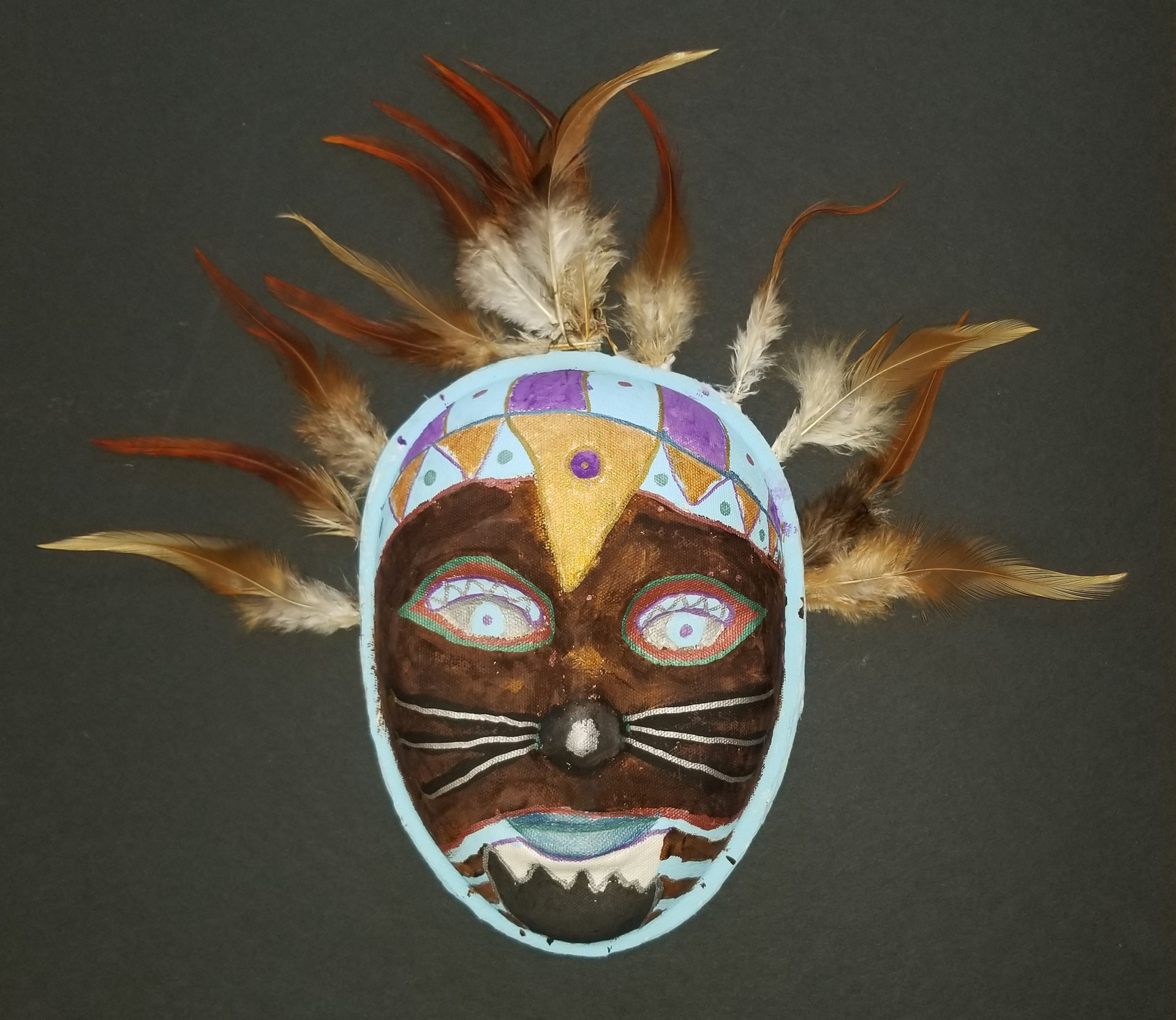 Mask sculpture with feathers