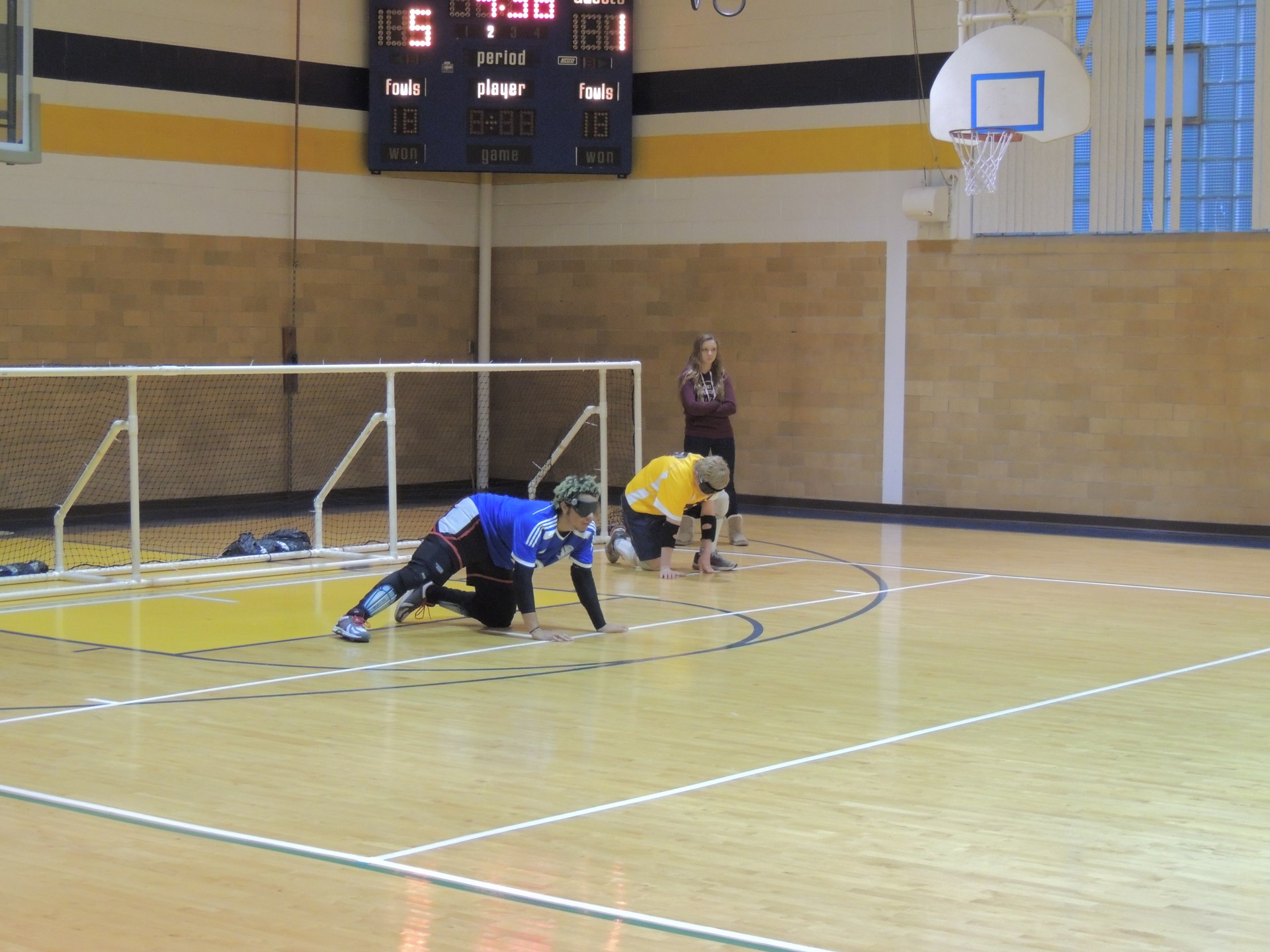 Two students kneeling in front of the Goalball goal to defend it.