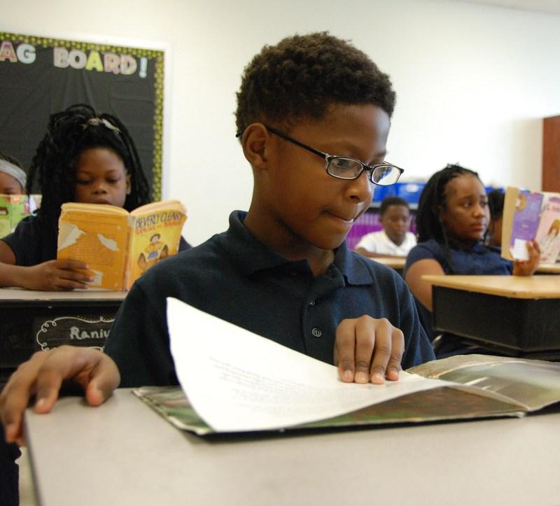 Boy reading at desk, CA-Old North