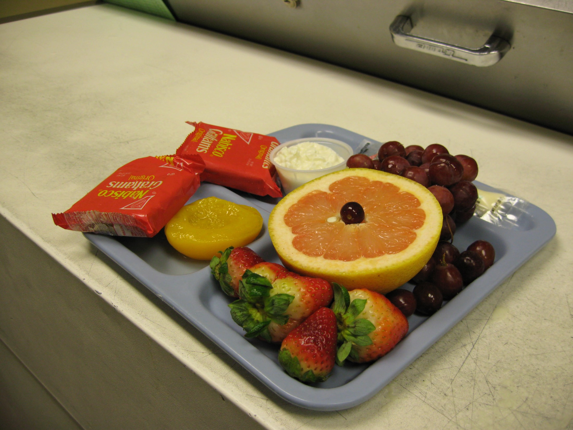 Lunch tray full of fruit and cheese.