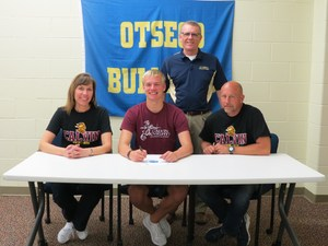 Trevor Sparks, with his parents and coach, signs to swim at Calvin.