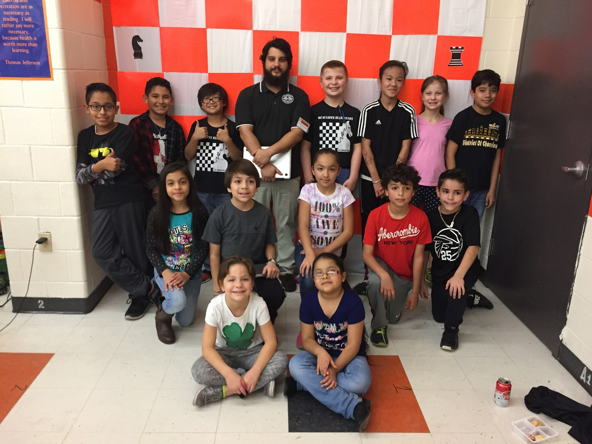 Students posing with Coach Mr. Morales at their chess tournament.