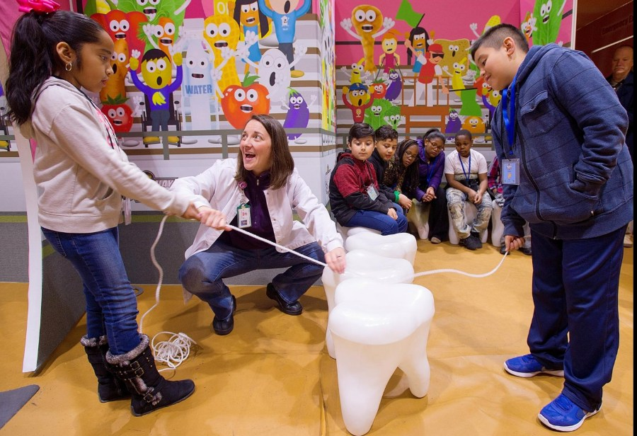 Carmen Carrick (center) teaches Keila Rodriguez and Andrew Chico how to floss teeth in the 'mouth' station at the 'Speedway to Healthy' exhibit held at the Davidson County Parks and Recreation Department on Thursday. [Donnie Roberts/The Dispatch]