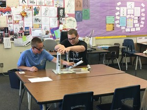 Students working on assembling their table structure out of newspapers.
