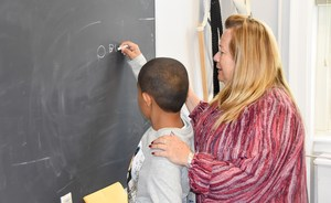 Van Cleve student writes on blackboard.