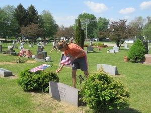 A TKMS students places an American flag on a grave site of a U.S. Veteran.