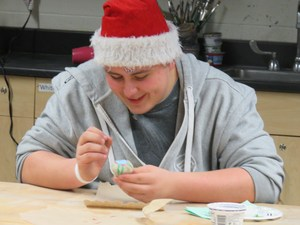 A TKHS student paints words of inspiration on a rock for hospice patients as part of the annual service learning day.