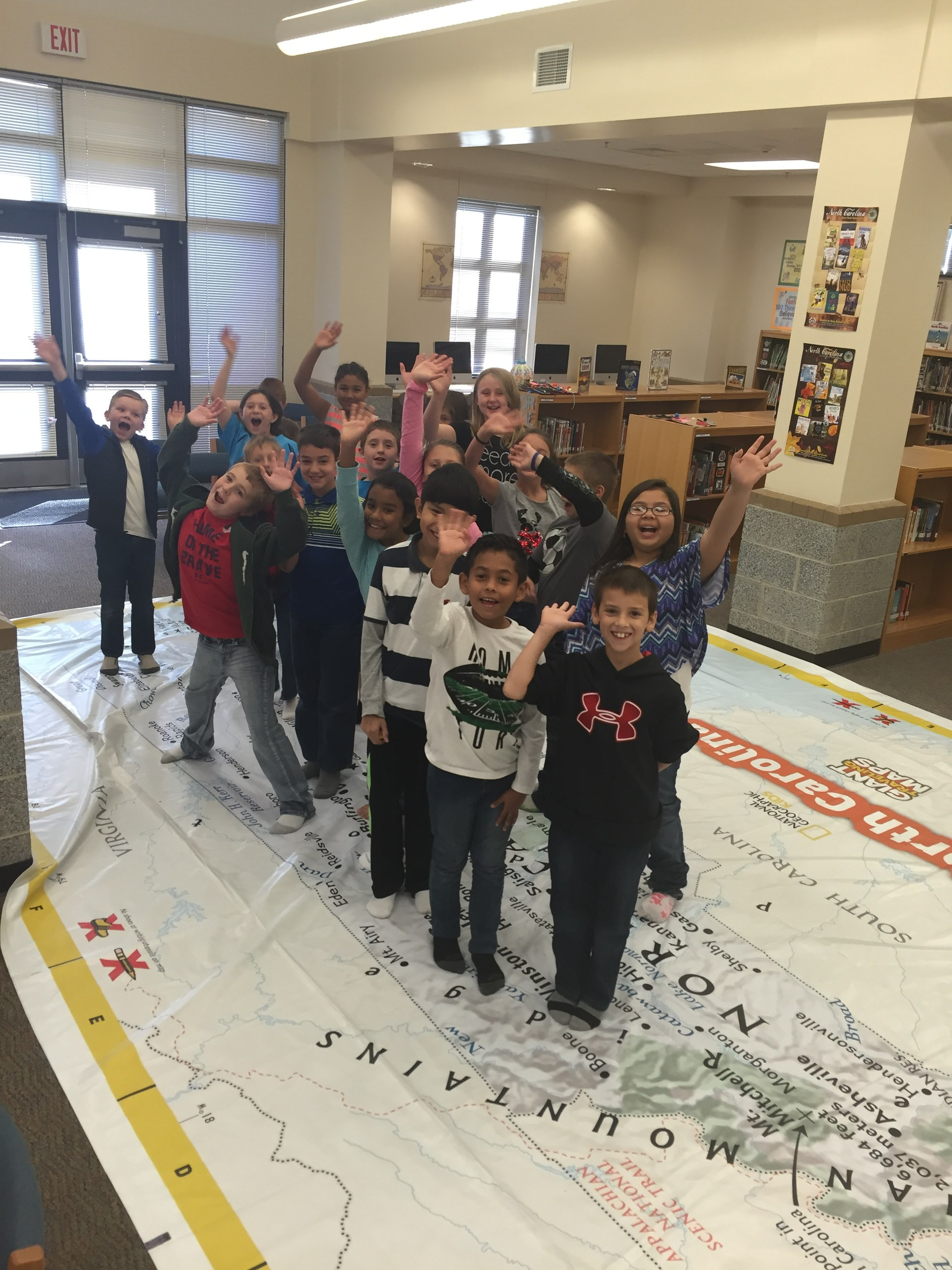 Class standing on giant map of NC.