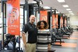 Coach and student athlete posing in weight room