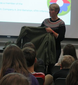 Middle School teacher Laura Nikkel shows students the jacket her father wore in Vietnam.