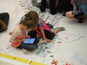 Two girls are using an iPad to find information about an area of the North Carolina map.
