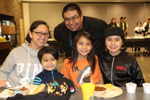 Family posing for a picture at the bean feed