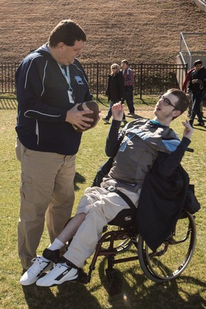 Coach Lancaster and Cole Kennington on the football field.