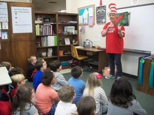 Staff member reads a Dr. Seuss book to students.