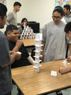 students constructing a tower from playing cards